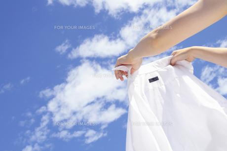 青空とワイシャツを干す女性の手の写真の素材 [FYI00412506]