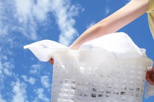 青空の下洗濯物を干す女性の手の写真の写真素材 [FYI00412515]