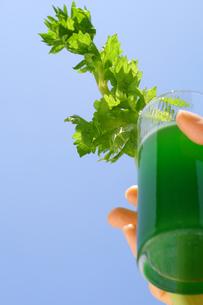 野菜ジュースとセロリを持つ女性の手の写真の素材 [FYI00412517]