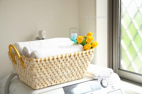 洗濯機の上の洗濯物と花飾りの写真の写真素材 [FYI00412534]