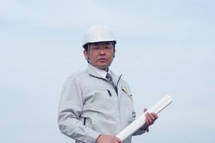 設計図面と作業服の日本人男性の写真の素材 [FYI00412557]