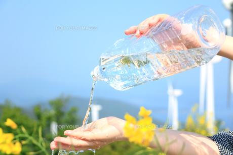 ペットボトルの流水を受ける女性の手と風力発電の写真の素材 [FYI00412574]