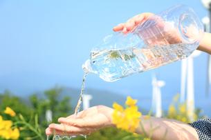 ペットボトルの流水を受ける女性の手と風力発電の写真の写真素材 [FYI00412574]
