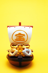 宝船と金銀財宝と巳年の干支人形 黄色背景の写真素材 [FYI00412623]