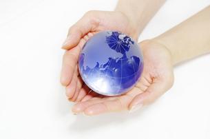 ガラスの地球儀を持つ女性の手の素材 [FYI00415537]