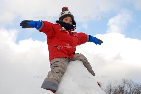 雪山で手を広げて遊ぶ子供の写真素材 [FYI00415768]