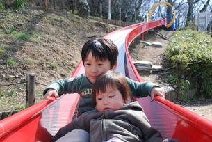 兄弟仲良く滑り台を滑るの写真素材 [FYI00415780]