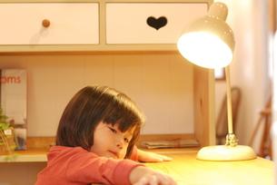 机で何かを考える子供の写真素材 [FYI00415814]