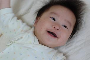 ベッドで笑う赤ちゃんの写真素材 [FYI00415829]