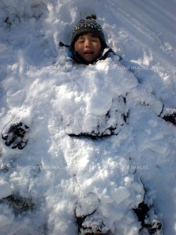 雪に埋まる男の子の写真素材 [FYI00416064]
