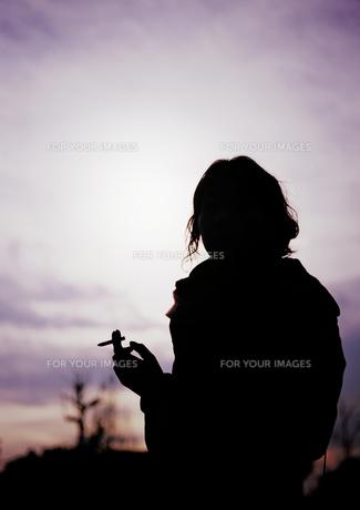 タバコを吸う若い女性のシルエットの写真素材 [FYI00416990]