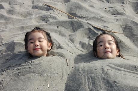 砂に埋もれる姉妹の写真素材 [FYI00419120]