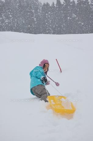 ソリをひいて雪山を登る少女2の写真素材 [FYI00419126]