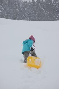 ソリをひいて雪山を登る少女の写真素材 [FYI00419128]