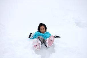 雪に埋もれて遊ぶ少女の写真素材 [FYI00419129]