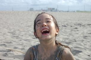 砂まみれで大笑いする少女の素材 [FYI00419136]