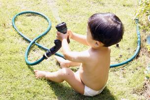 庭で水遊びをする赤ちゃんの写真素材 [FYI00420867]