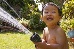 庭で水遊びをする赤ちゃんの写真素材 [FYI00420871]