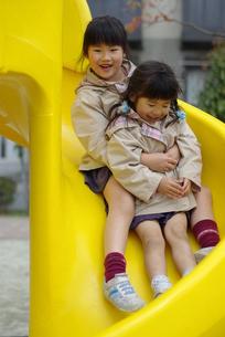 滑り台で遊ぶ姉妹の写真素材 [FYI00421256]