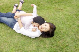 芝生に寝転ぶ親子の写真素材 [FYI00425227]