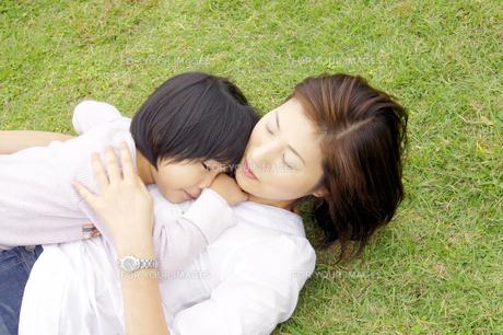 芝生に寝転ぶ親子の写真素材 [FYI00425228]