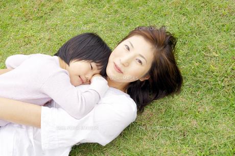 芝生で寝転ぶ親子の写真素材 [FYI00425233]