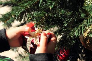 クリスマスツリーと飾り付けをする子供の手の写真素材 [FYI00428333]