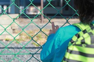 フェンスを掴む子どもの後ろ姿の写真素材 [FYI00429970]