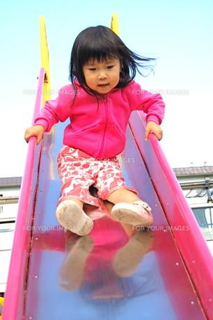 滑り台を滑る、女の子の写真素材 [FYI00430313]