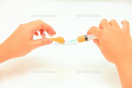 注射器でアンプルから薬を吸うの写真素材 [FYI00430769]