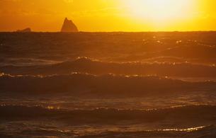 荒波と夕日と小島の写真素材 [FYI00434849]