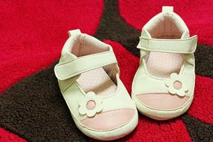 赤いマットと赤ちゃんの靴の素材 [FYI00436172]
