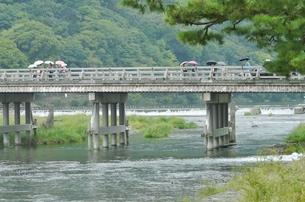 渡月橋を渡る傘の写真素材 [FYI00439024]