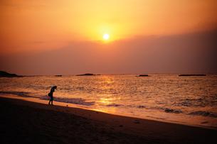 夕焼けのニシハマと女性の写真素材 [FYI00448144]