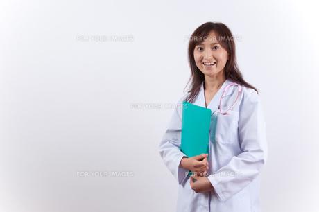 笑顔のファイルを持った白衣の女医の写真素材 [FYI00448214]