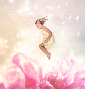 大きな花の上を跳んでいる女の子の写真素材 [FYI00449557]