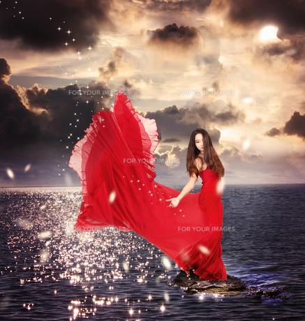 海にいる赤いドレスを着た女性の写真素材 [FYI00449558]