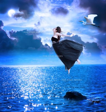 月夜の海にジャンプをしている女性の写真素材 [FYI00449561]