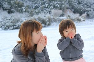 手に息を吹きかける親子の写真素材 [FYI00456648]