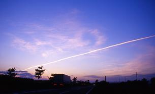 暁の飛行機雲とトラックの写真素材 [FYI00456681]
