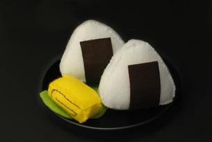 おにぎりと卵焼きの手作りおもちゃ 黒バックの写真素材 [FYI00456754]
