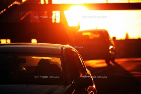 夕陽を背に走る車の素材 [FYI00458579]