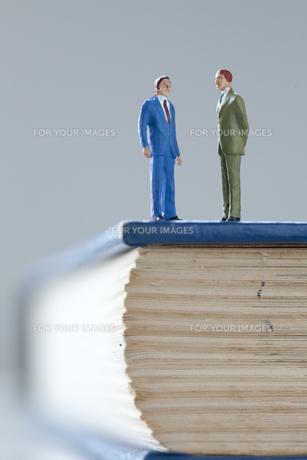 辞書の上のビジネスマンの写真素材 [FYI00460162]