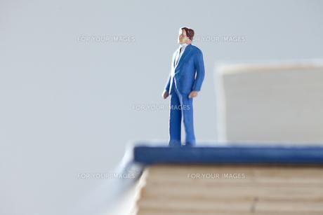 辞書の上のビジネスマンの写真素材 [FYI00460172]