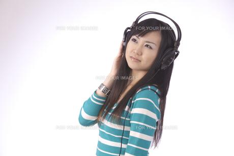 ヘッドホンで 音楽を聴く 若い女性の写真素材 [FYI00461364]