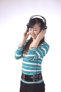 ヘッドホンで 音楽を聴く 若い女性の写真素材 [FYI00461376]