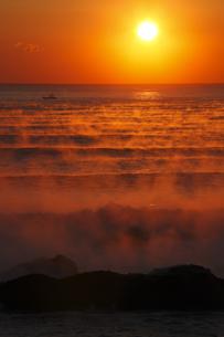 気嵐 毛嵐の海に昇る太陽 冬の風物詩 幻想的光景の写真素材 [FYI00461440]
