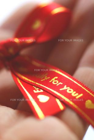 手のひらの赤いリボンの写真素材 [FYI00461806]