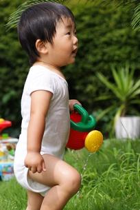 じょうろで水遊びをする幼児の写真素材 [FYI00461836]