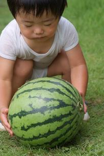 大きな西瓜を抱える幼児の写真素材 [FYI00461837]